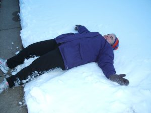Arona-making-a-snow-angel-on-her-front-lawn
